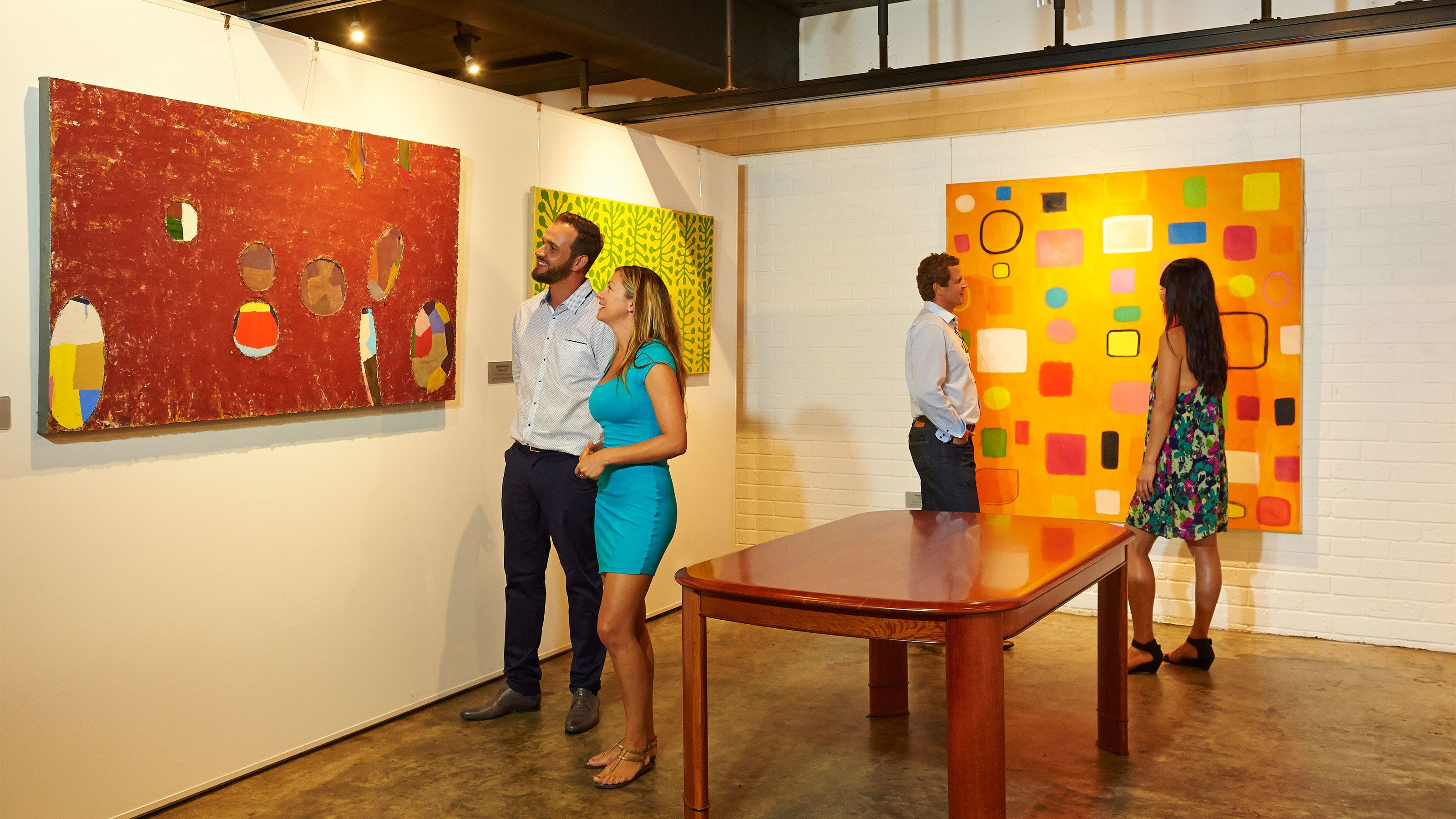 Two couples viewing featured art in gallery.