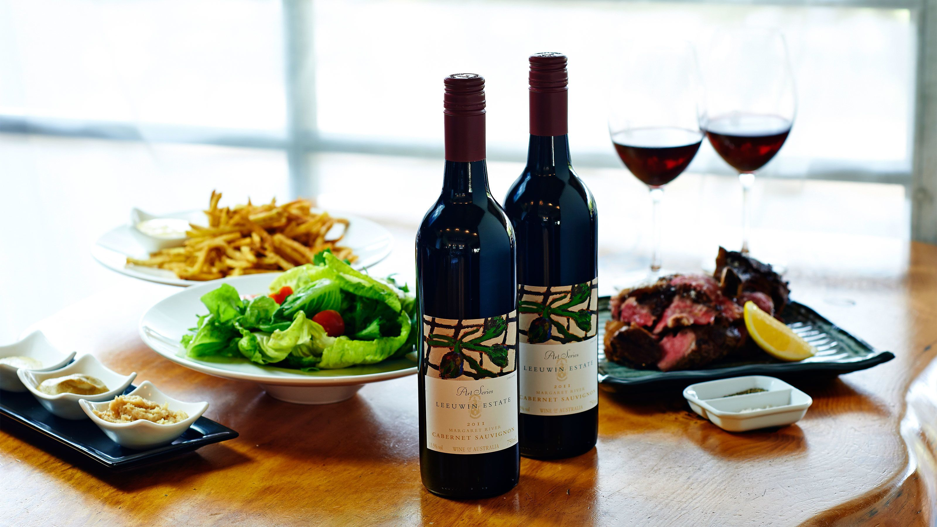 Close up of wooden table with two bottles of red wine, two filled glasses, and food.