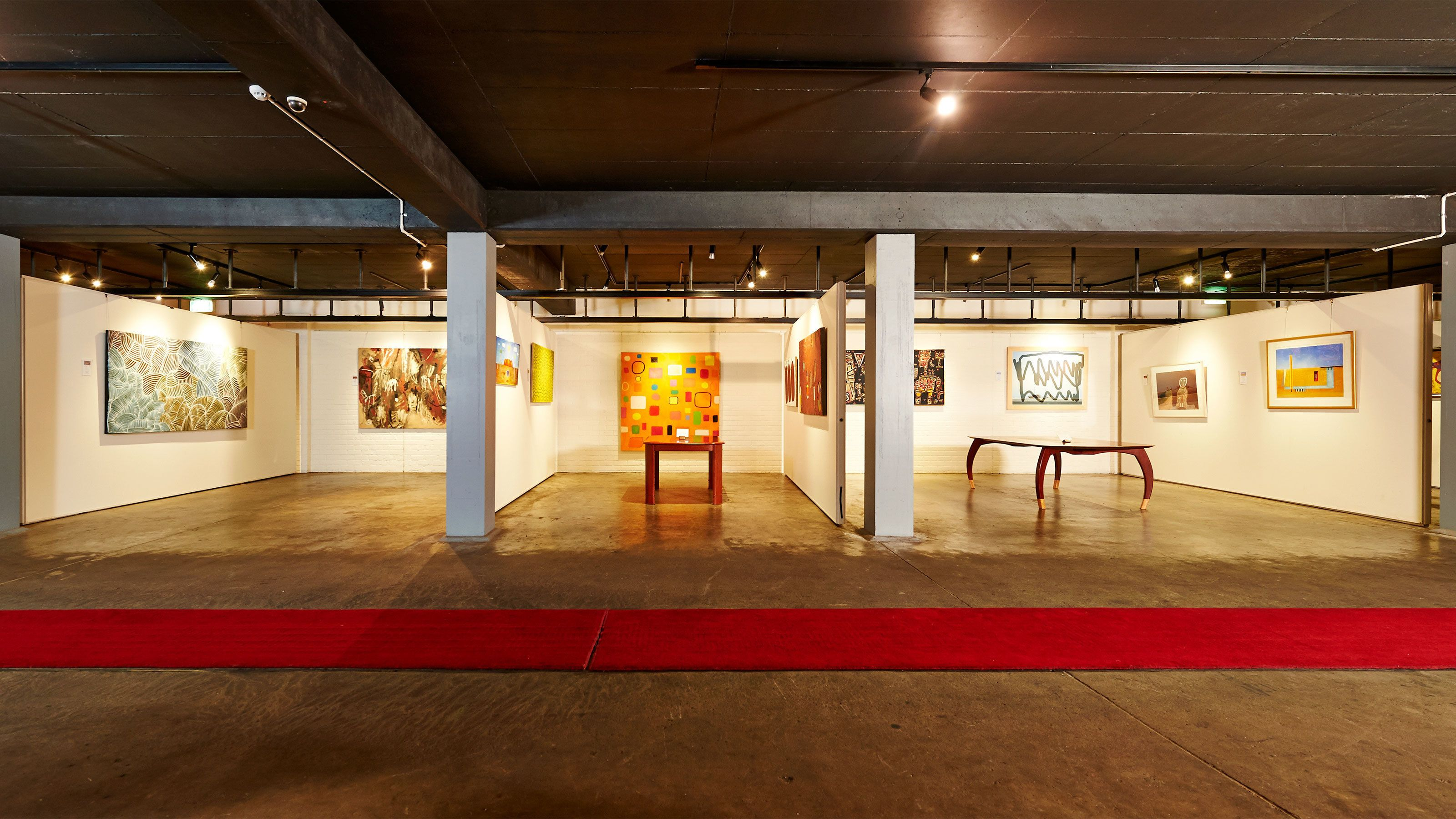 Wide view of lit up art gallery with smooth concrete flooring.
