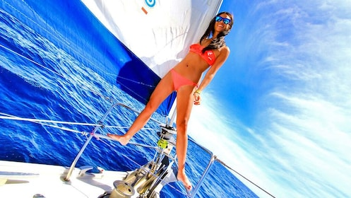 Woman standing on the rails of a sailboat in Los Cabos