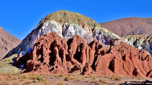 Layers of colorful rock in a hill in Rainbow Valley