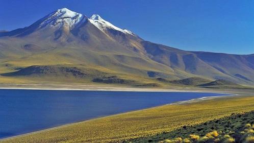 Lake with snow covered mountain peak in background in San Pedro de Atacama