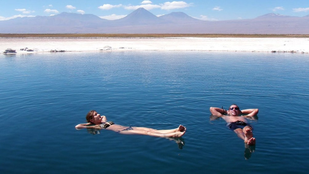 Show item 2 of 5. Swimming couple in a lagoon in Chile