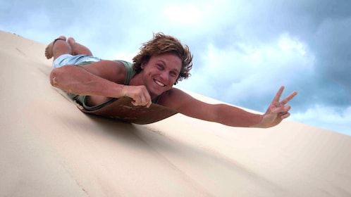 Man bodysurfing down sand dune on Moreton Island