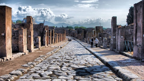 Ruins of pillars line a stone street in Pompeii