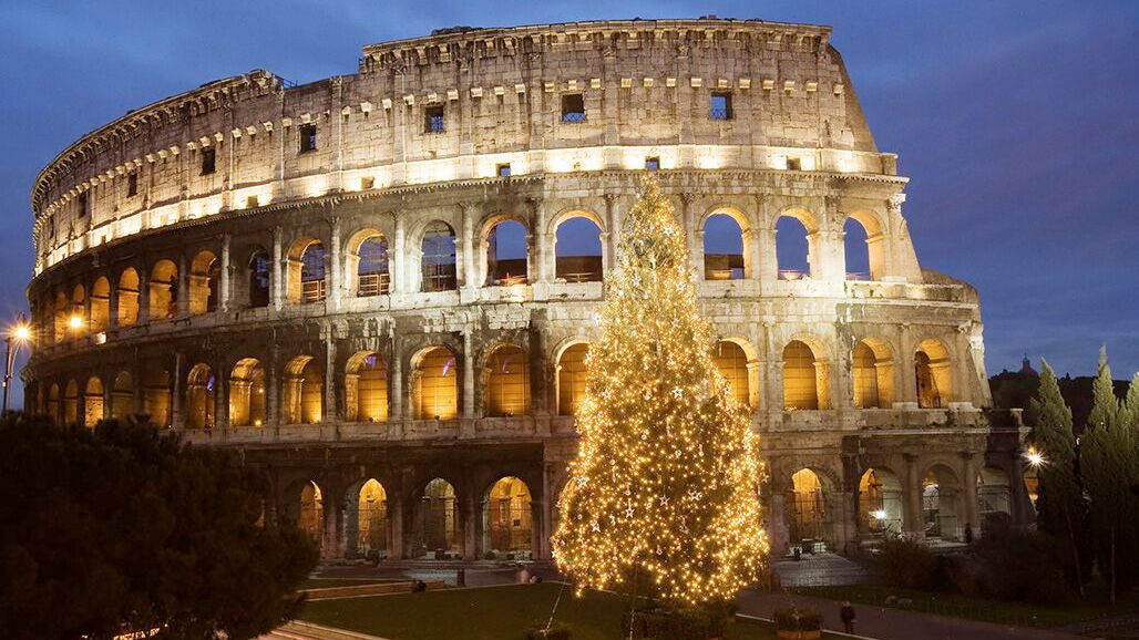 Christmas tree lit at night in front of the Colosseum in Rome