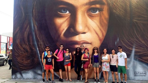 Tour group stands in front of large portrait on wall in New York