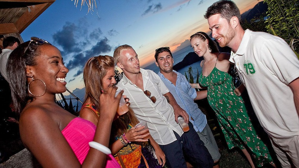 Show item 4 of 7. Partygoers enjoying party refreshments at sunset in Antigua