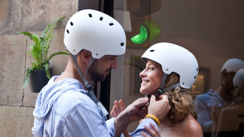 Couple fastening their helmets in preparation for the Ciutadella Park & Born District Segway Tour