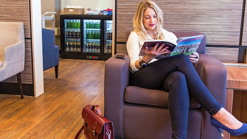 woman reading magazine at the Aspire airport lounge