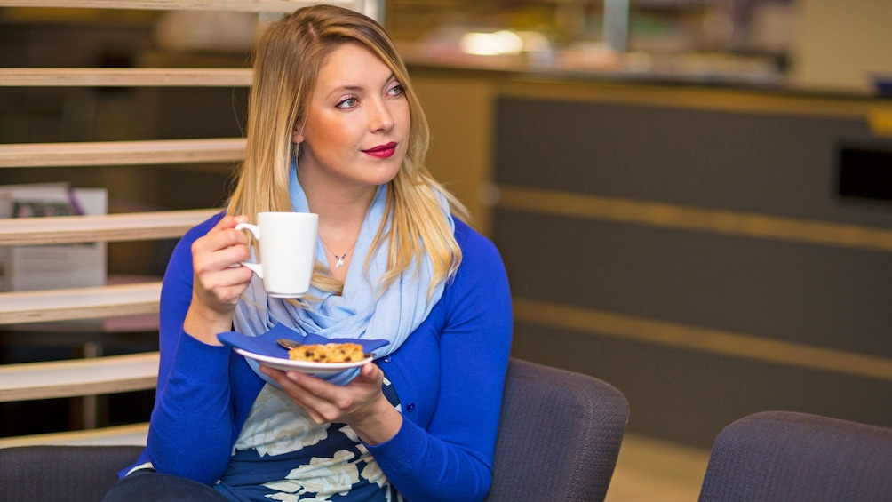 woman relaxing with a cup of coffee at the Aspire airport lounge