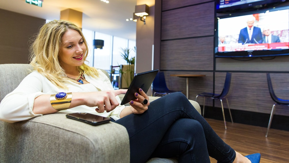 Öppna foto 3 av 5. woman reading from her tablet device at the Aspire airport Lounge