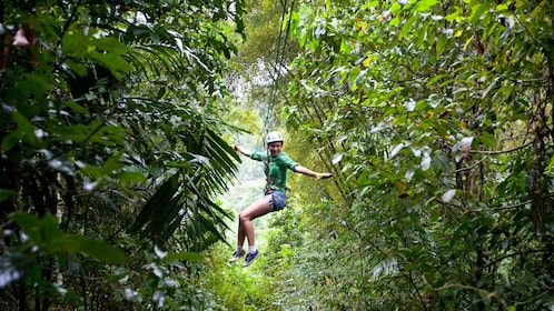 ziplining woman extending out arms for balance in Saint Lucia