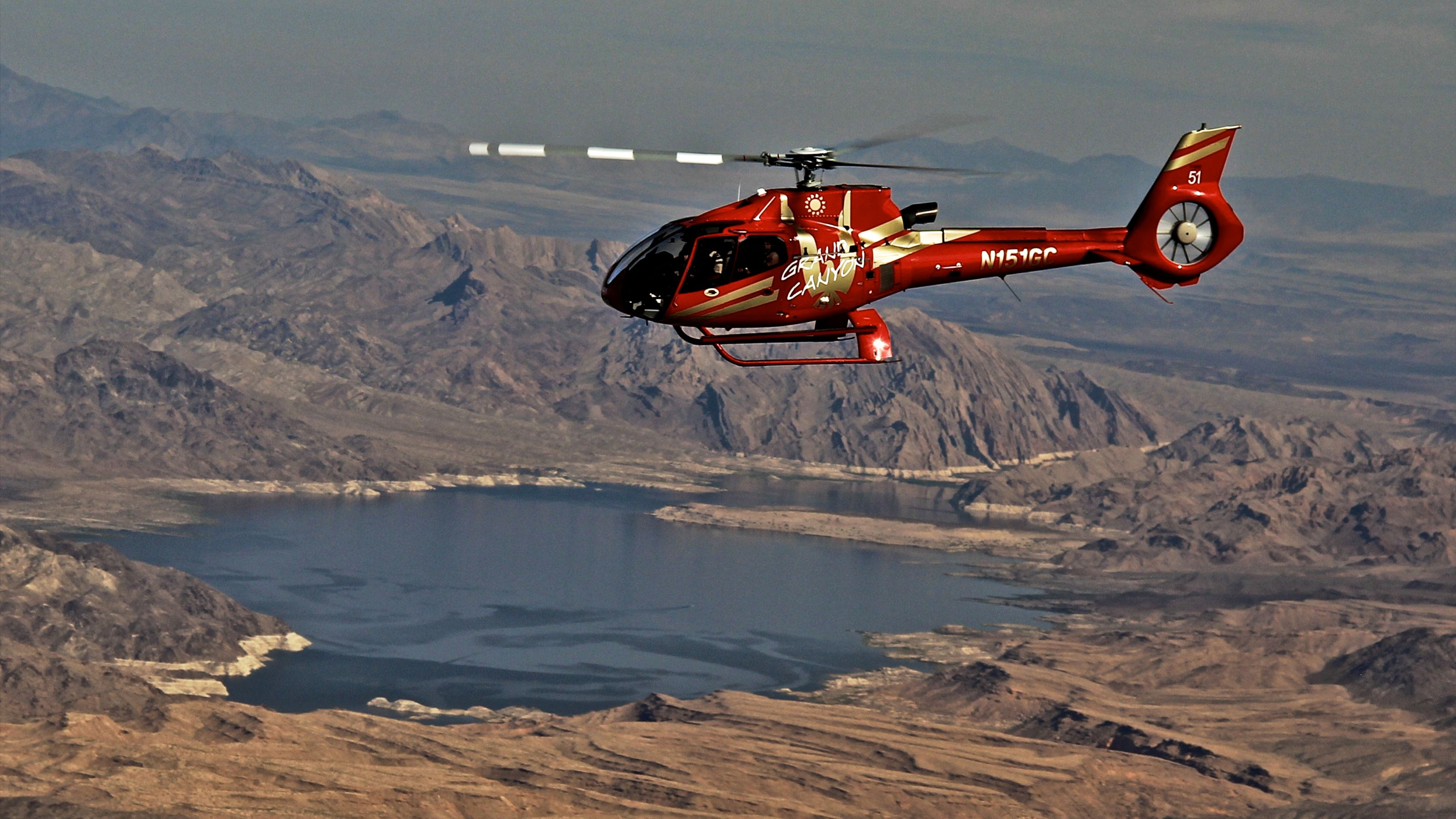 red helicopter flying over mountainous area in nevada