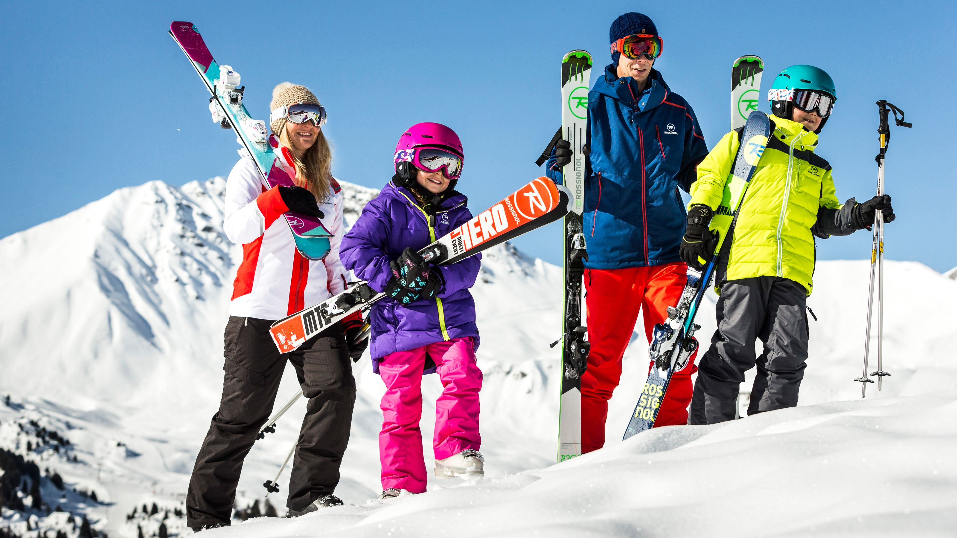 Family preparing to ski down the slopes on a sunny afternoon