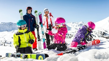 Show item 2 of 5. Family preparing for an exciting afternoon skiing on the mountain slopes