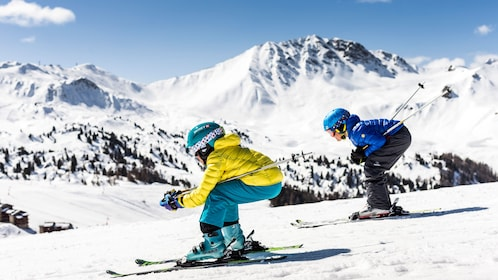 Two kids skiing down a steep mountain slope