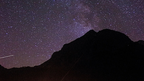 Silhouette of a a mountain with stars above