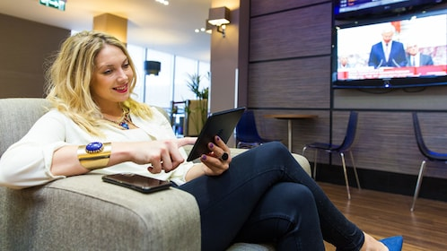 woman reading her tablet device at the airport lounge