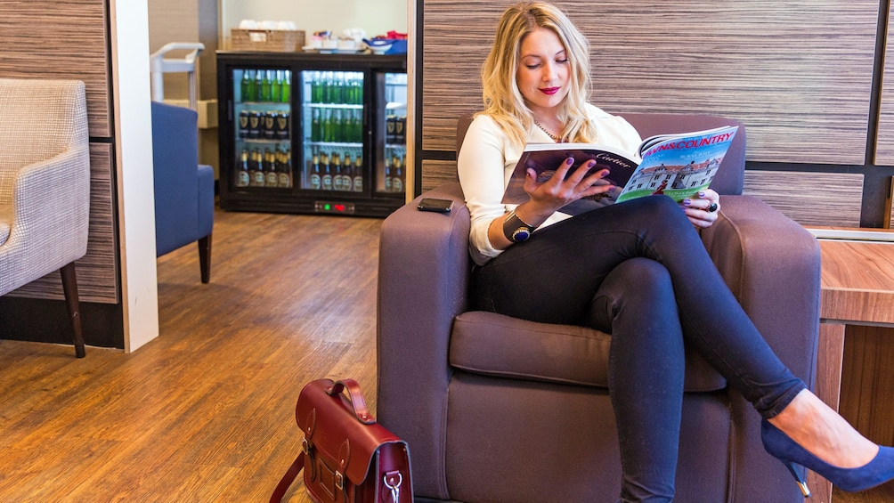 Show item 3 of 5. woman reading magazine at the airport lounge