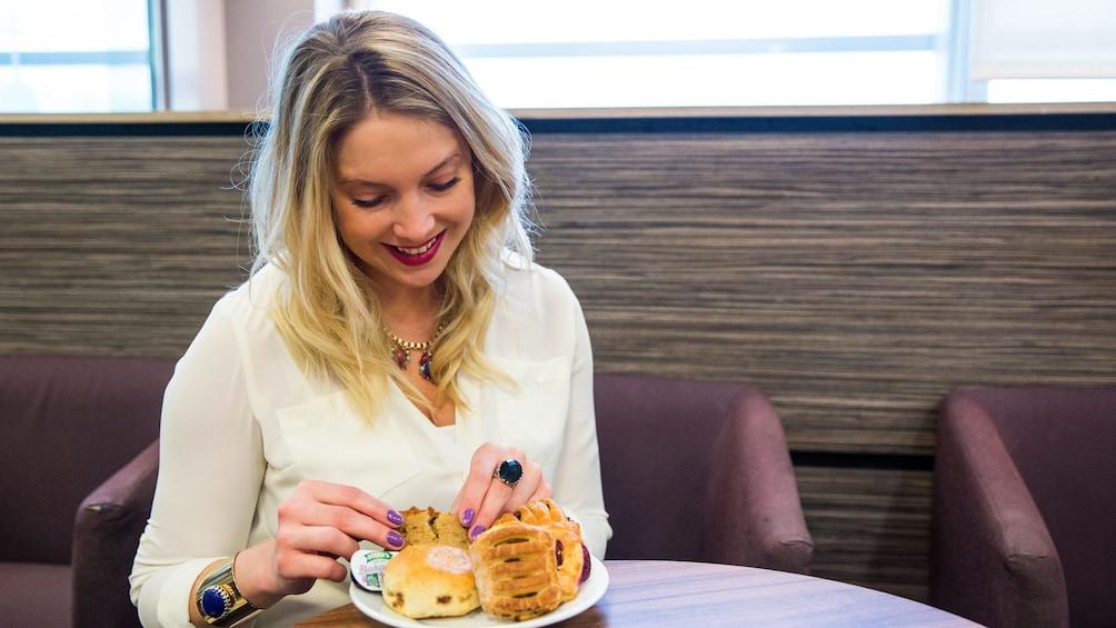 Öppna foto 4 av 5. woman enjoying pastries at the airport lounge
