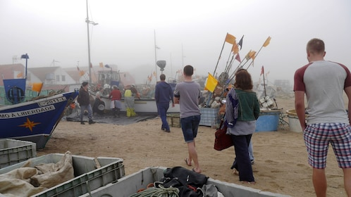 People walking through boats and fishing gear on a foggy day
