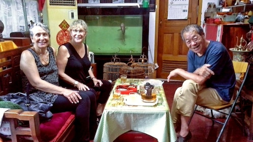 Two tourists eat food with a local in Beijing