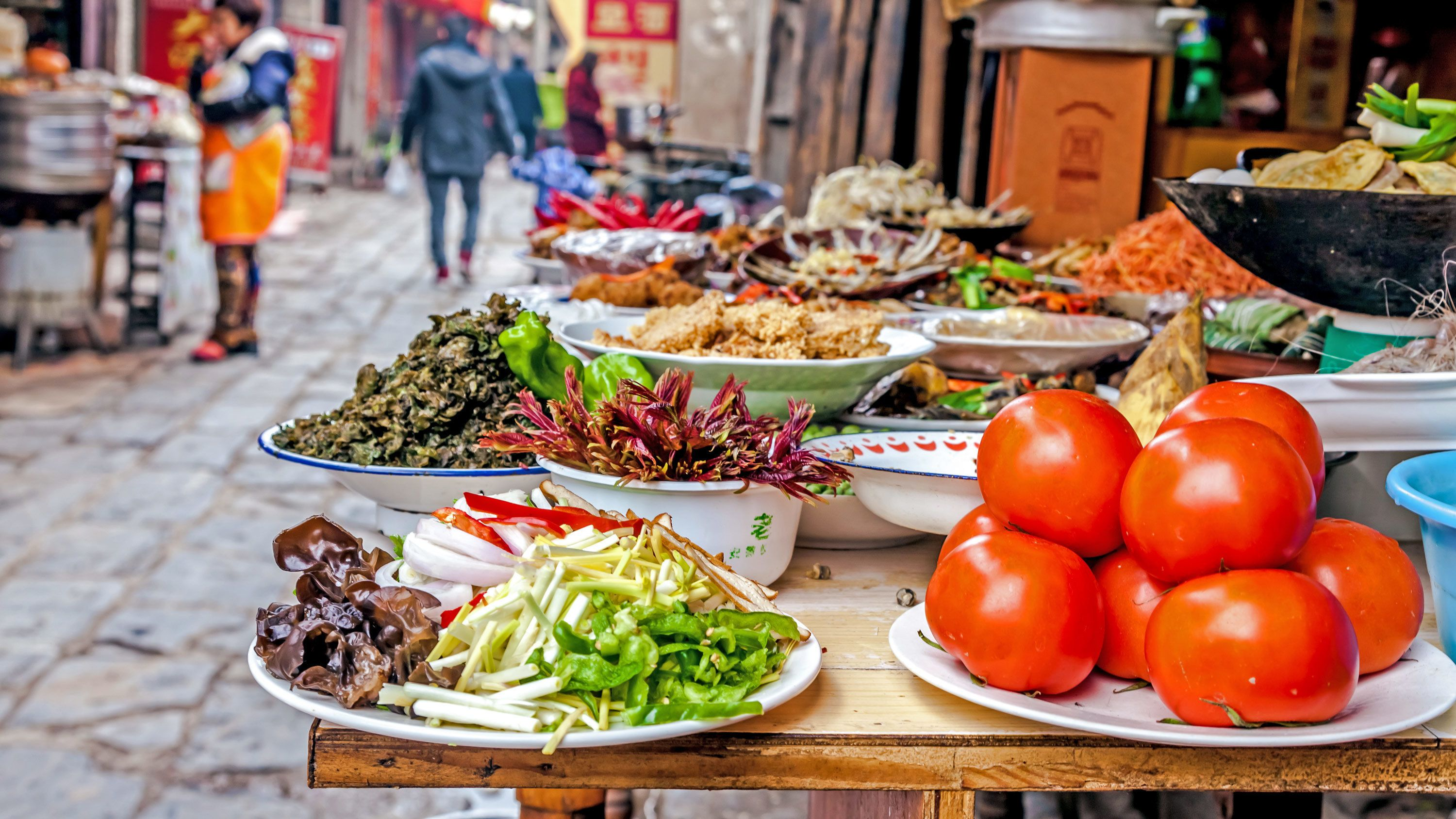 A table of produce on plates in a Beijing alley