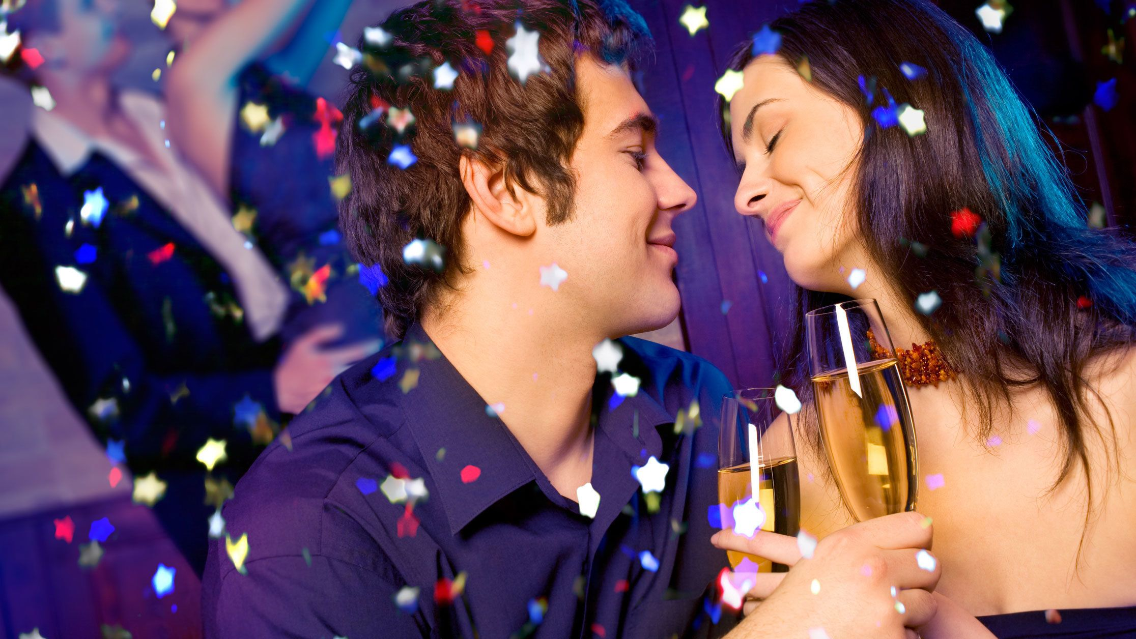 Two people toast during party with confetti falling
