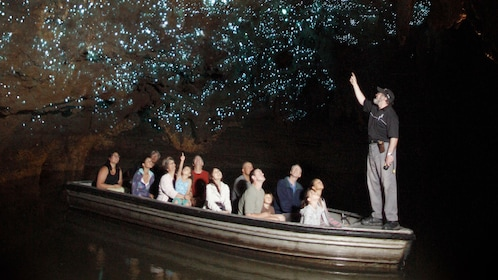 Guide points out cave phosphorescence to boat full of people