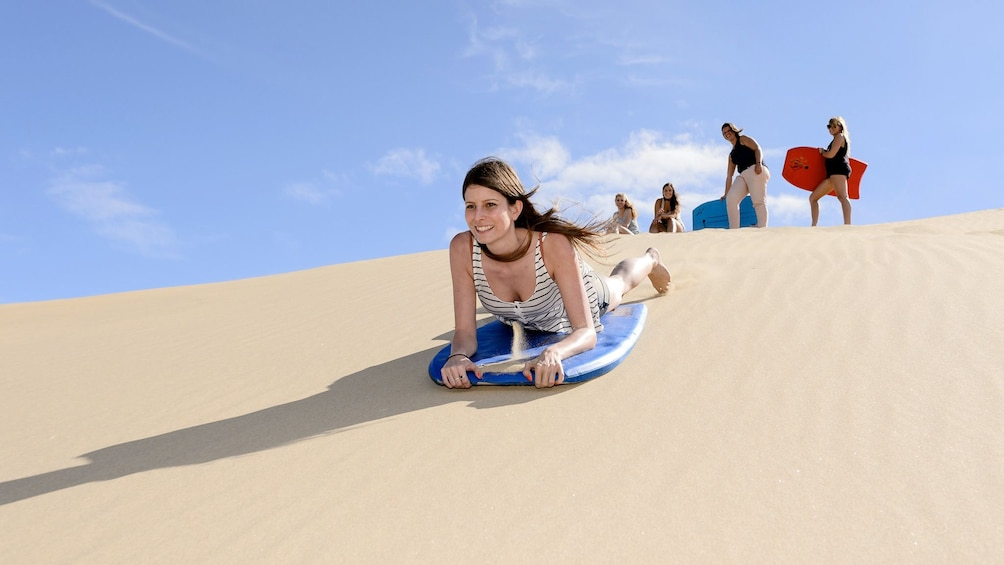 Show item 5 of 8. Woman rides a Boogie board down a sand dune