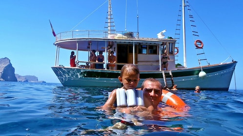 Father and daughter swim next to anchored boat in Pollensa Bay