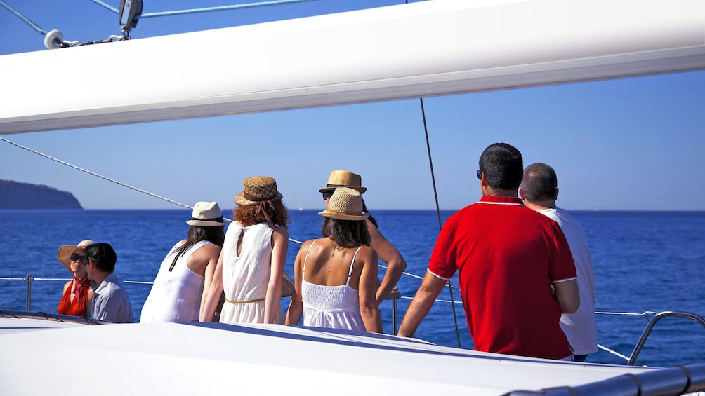 People look out to sea on deck of Catamaran