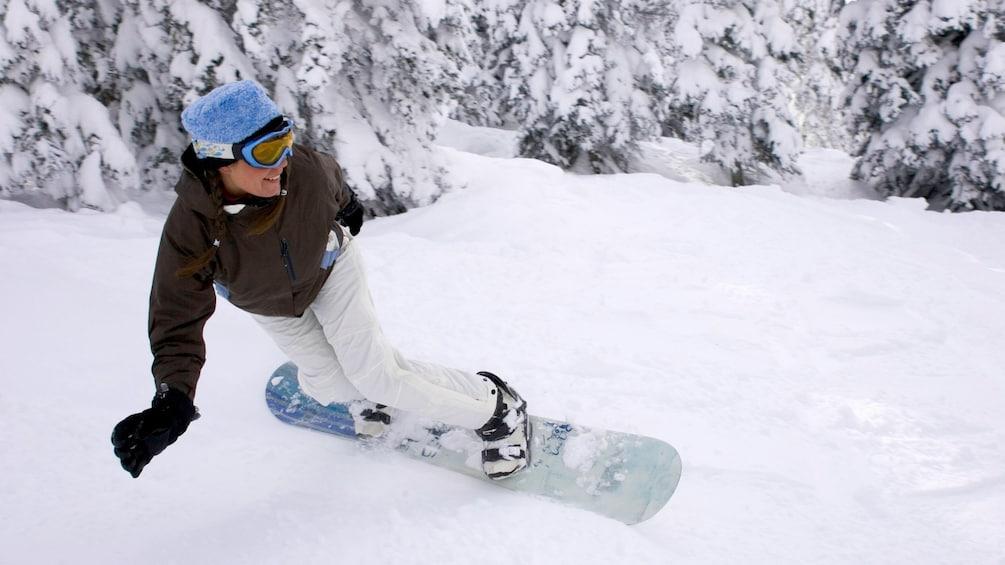 Foto 2 van 5. Snowboarder traversing down a slope