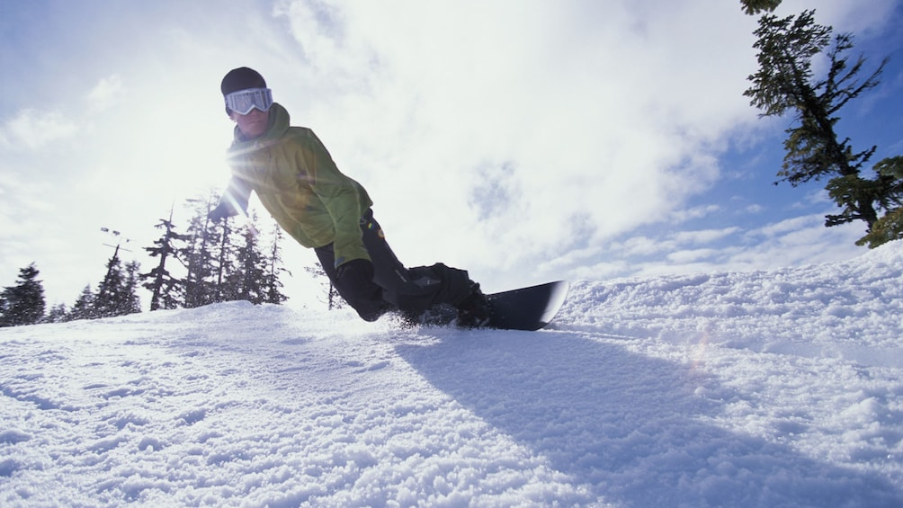 Foto 1 van 5. Snowboarder gliding down a slope on a bright afternoon
