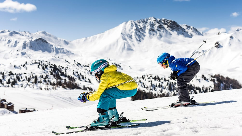 Show item 1 of 5. Two kids skiing down a steep mountain slope