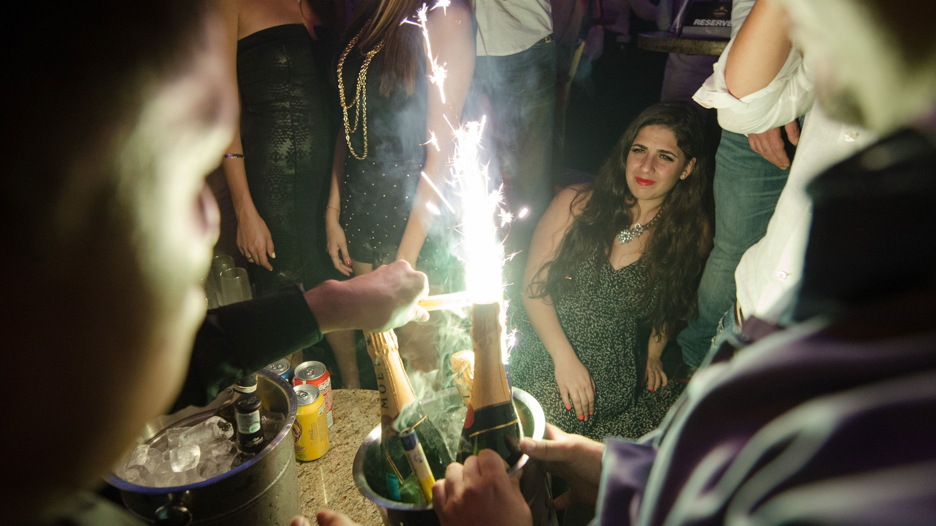 Sparklers being lit over glasses of champagne.