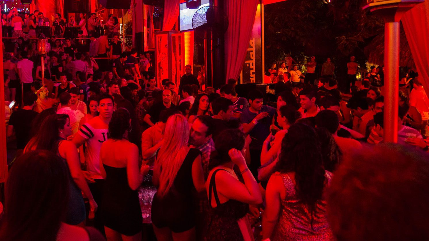 Interior view of nightclub partygoers dancing and socializing.