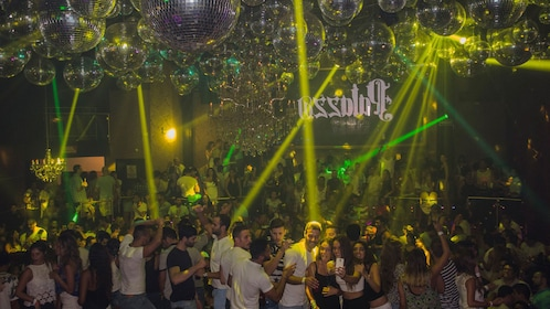 Interior view of night club with several disco balls and partygoers socializing and dancing.