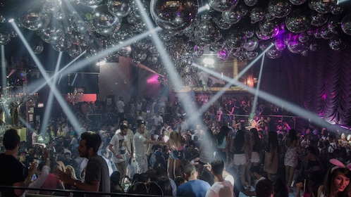 Interior view of night club with several disco balls and partygoers.