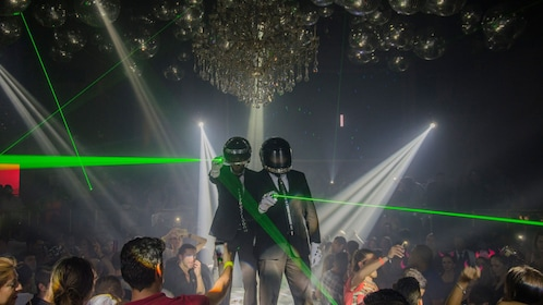 Performers on stage with laser beams at night club.