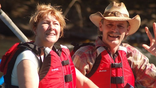 Close up of man and woman wearing life jackets.