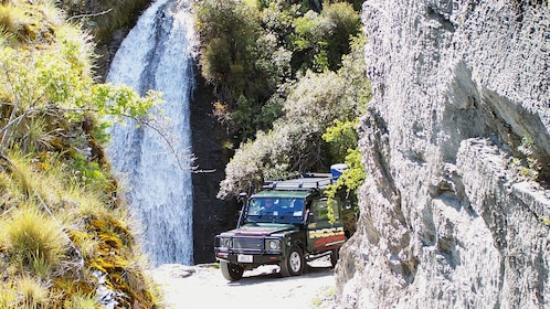 Jeep on a dirt road with waterfall nearby in Queenstown