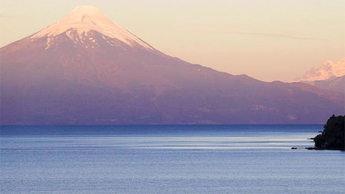 Large body of water with snowy volcano in distance.