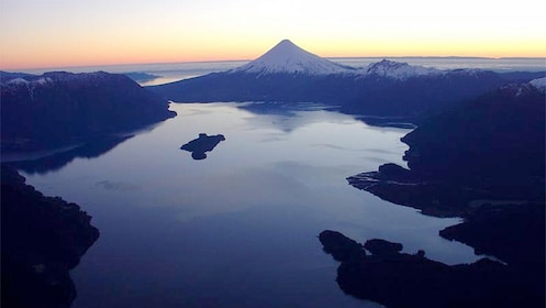 Aerial view of lake with volcano in the distance at sunset.