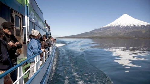 Tourists on ferry boat observing large volcano in the distance.