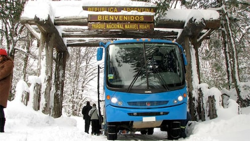 Bus parked under welcome sign in snowy area.