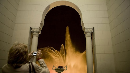 Tourist captures a photo of the illuminated fountains on display at the Magic Circuit Water Show