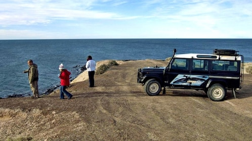 Tourists near a parked jeep along the coast in Argentina