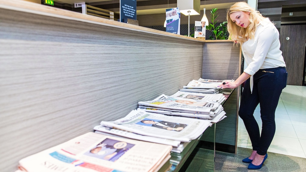 Show item 1 of 5. woman sifting through papers at the news stand at the airport lounge